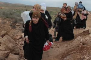 A group of Syrian refugees cross into Jordan using one of the 43 paths that cross the southern Syrian border on 18 February 2012.  New arrivals are directed into a shelter near the Jordanian border guard outpost, a few meters from the border, before they are taken to the Za'atari refugee camp. UNHCR / N. Daoud