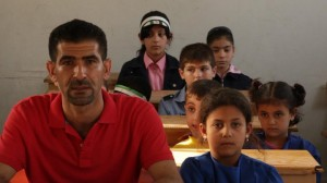 Tamer Alawam with kids in a school in Maarat an-Numan, Syria